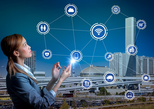 IOT girl with icons and city background iStock 691792716 Small 640x400